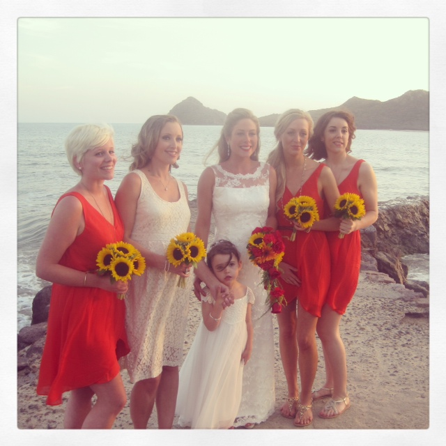 The bridesmaid held simple sunflower posies on the beach.